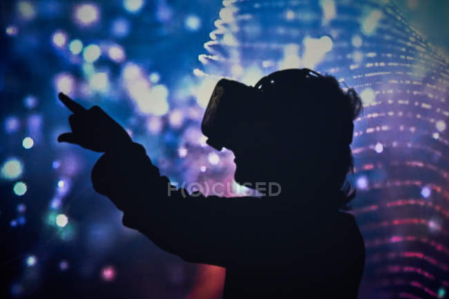 Silhouette of child wearing virtual glasses at home with colored light effects — Stock Photo