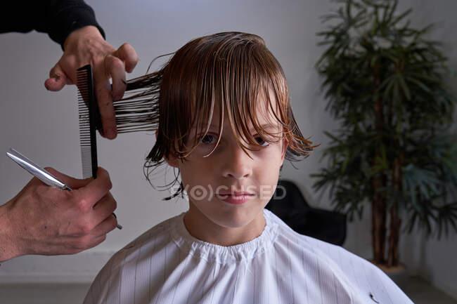 Ragazzo che si taglia i capelli da un parrucchiere — Foto stock