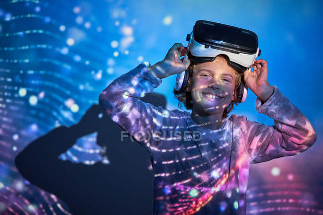 Child with virtual glasses at home with colored light effects, looking in camera — Stock Photo