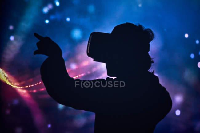 Силует дитини з віртуальними окулярами вдома з кольоровими світловими ефектами. — стокове фото