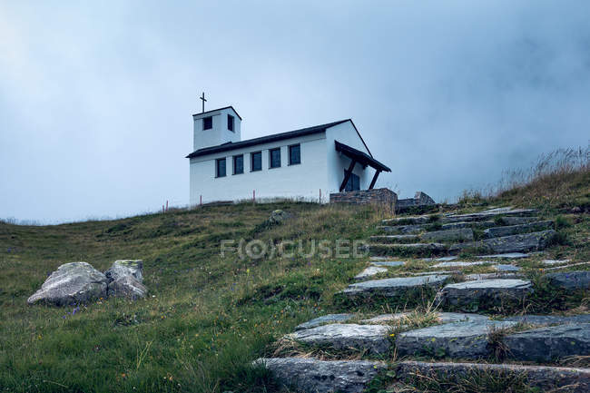 Charming landscape of small white church on top of green valley with stony way up in Austria — Stock Photo