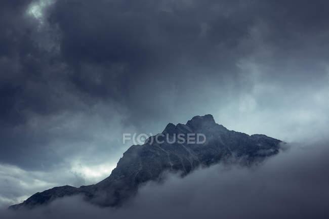 Cumbre rocosa misteriosa y dramática bajo nubes grises en un niebla nebulosa en Austria. - foto de stock