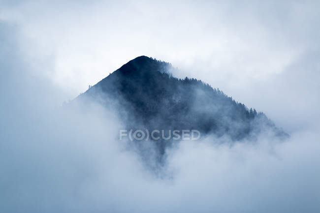 Dramatic mysterious rocky peak under gray clouds in foggy mist in Austria — Stock Photo