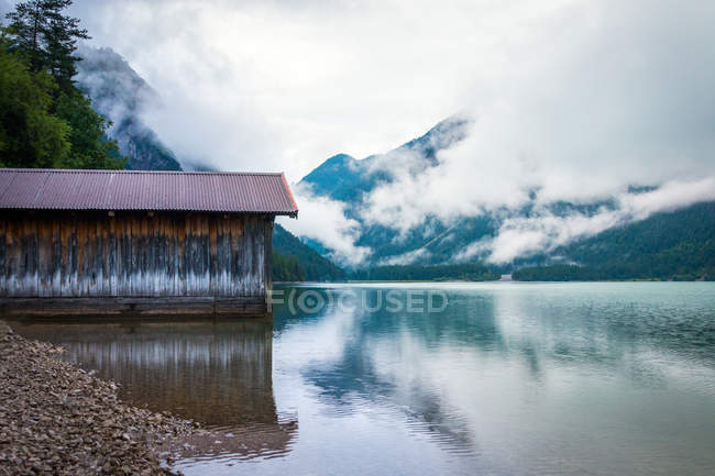 Shabby shed for boats located near tranquil water of pond near mountain ridge on cloudy day in Austria — Stock Photo