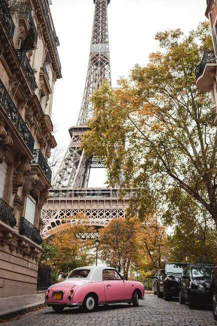 Desde abajo Torre Eiffel y coche antiguo rosa en la calle de Francia en otoño - foto de stock