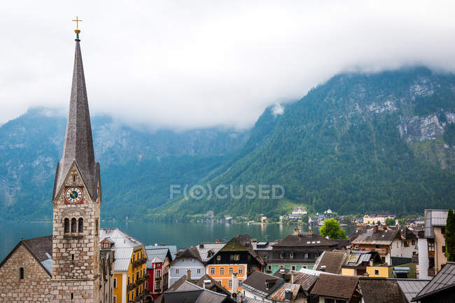 Clean pond with tranquil water and lovely houses of small town located near mountain ridge on cloudy day in Austria — Stock Photo
