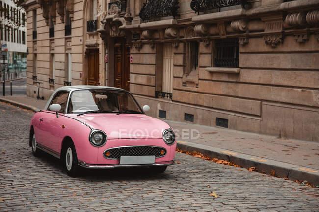 Розовый ретро-автомобиль припарковался на улице старого города в Париже в пасмурный осенний день — стоковое фото