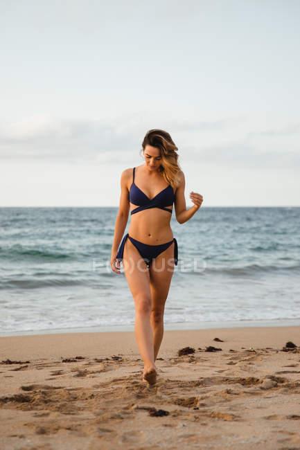 Женщина в купальниках смотрит вниз и идет по песчаному берегу на фоне волнистого моря и облачного неба — стоковое фото