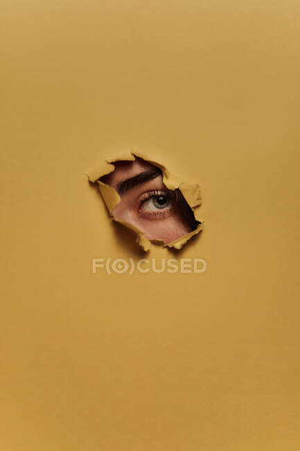 Анонімні люди дивляться через паперову діру. — стокове фото