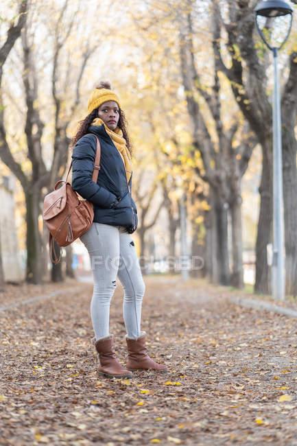 Захоплива афро-американська жінка в жовтому капелюсі і теплий піджак зі шкіряним рюкзаком і руками в кишені, дивлячись на камеру з посмішкою на дорожньому осінньому парку — стокове фото