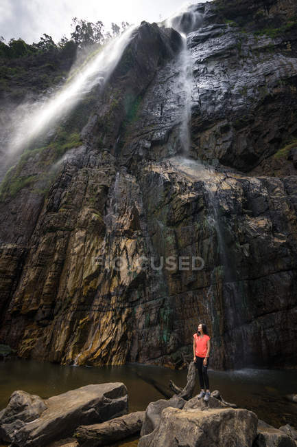 Woman standing on stone near powerful waterfall streaming from mountains — Stock Photo