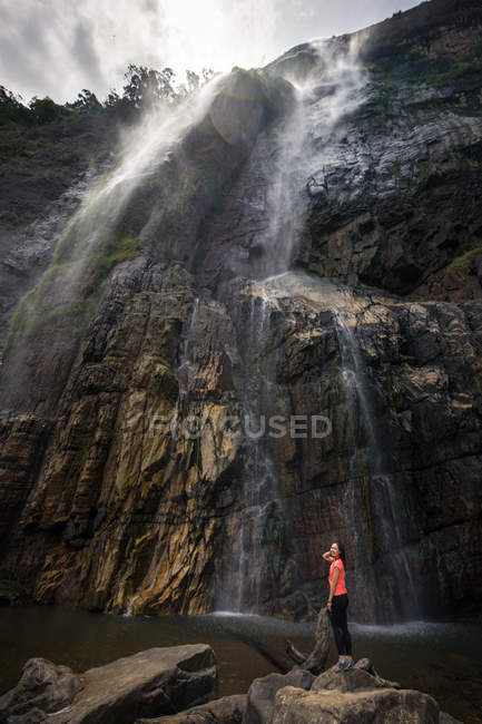Foamy strong waterfall streaming from rocky mountain before small woman standing on stones in cloudy day in Diyaluma Falls, Sri Lanka — Stock Photo