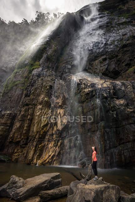 Donna in piedi sulla pietra vicino potente cascata che scorre dalle montagne — Foto stock