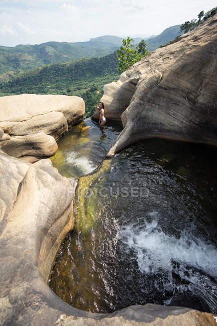 Ispirato donna nuoto in piscina sassosa in cascata di montagna — Foto stock