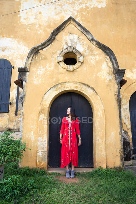 Curious female tourist in dress sightseeing old building — Stock Photo