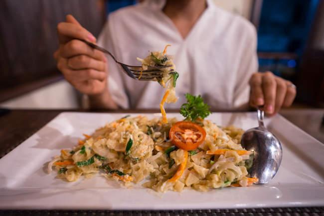Abgeschnittenes Bild einer Frau, die im Restaurant leckeres exotisches Gericht isst — Stockfoto