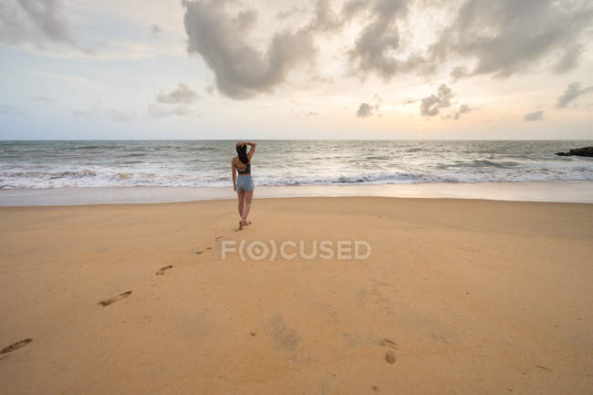 Back view of woman on vacation in casual wear enjoying view while walking at sandy empty seashore at Negombo beach — Stock Photo