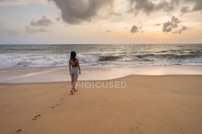 Vue arrière de la femme en vacances en tenue décontractée profitant de la vue tout en marchant au bord de la mer sablonneuse vide à la plage de Negombo — Photo de stock