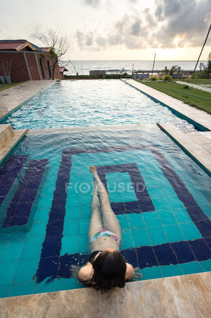 Back view of woman in swimsuit having relaxation in swimming pool at Negombo Beach hotel at Sri Lanka — Stock Photo