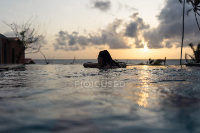Back view of woman enjoying water while swimming in pool with beautiful cloudy sky on sunset at Negombo Beach hotel at Sri Lanka — Stock Photo