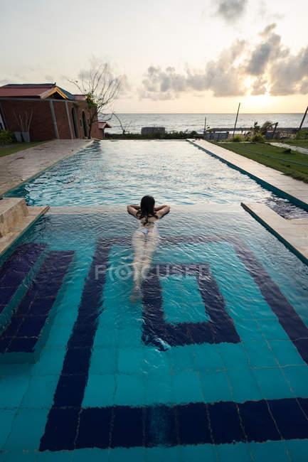 Female traveler in swimsuit resting in pool at resort — Stock Photo