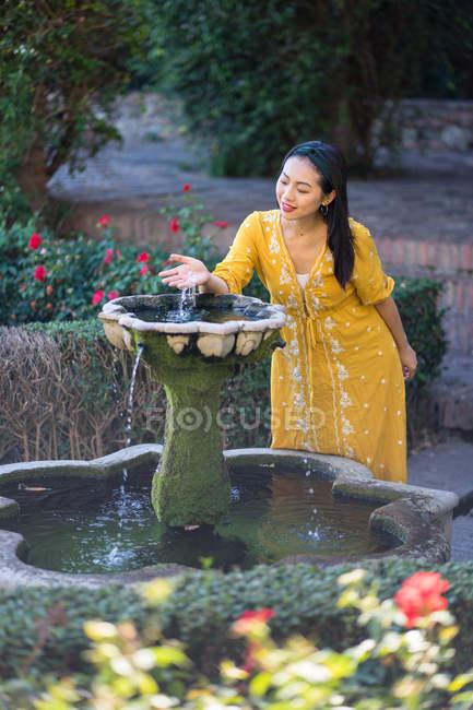 Mulher asiática tocando água da fonte no jardim — Fotografia de Stock