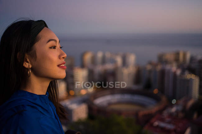 Happy asian tourist against city and sunset sky — Stock Photo