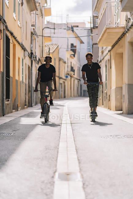 Un joven y alegre hombre afroamericano que monta un scooter eléctrico mientras el hombre negro conduce en bicicleta por la calle mirando la cámara. - foto de stock
