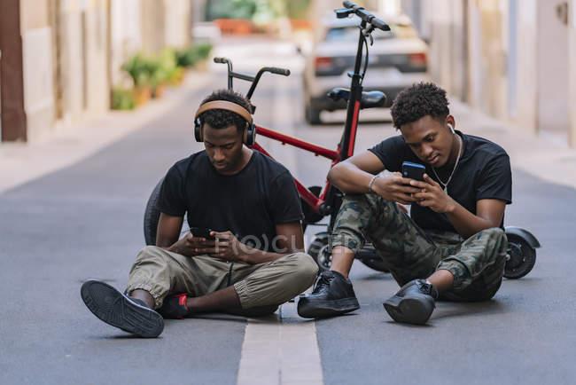 Allegro giovane afroamericano maschio adolescente condividere le immagini su telefoni cellulari con gioioso nero maschio amico in cuffie — Foto stock