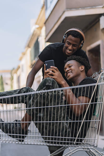 Happy young African American man in casual clothes sitting in cart and sharing messages on smartphone with black male friend in headphones during pastime together in street — Stock Photo