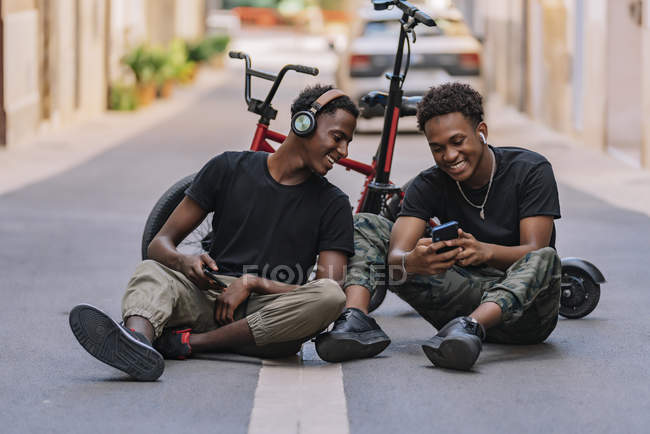 Cheerful youthful African American male teenager sharing pictures on cellphone with joyful black male friend in headphones — Stock Photo