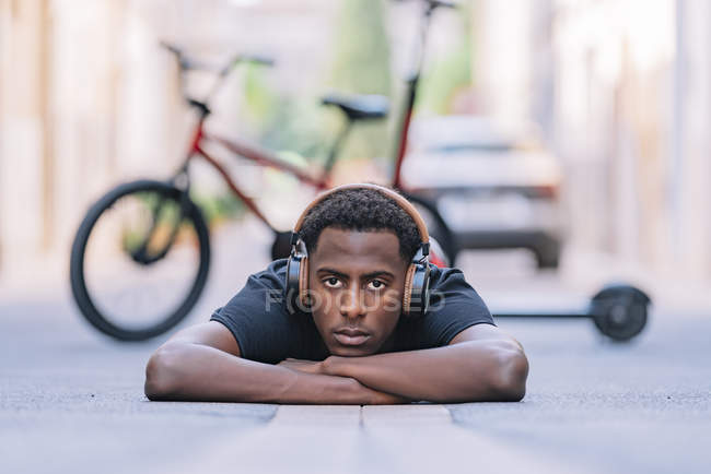 Concentrated youthful African American man wearing headphones listening to music while lying on asphalt road in street — Stock Photo