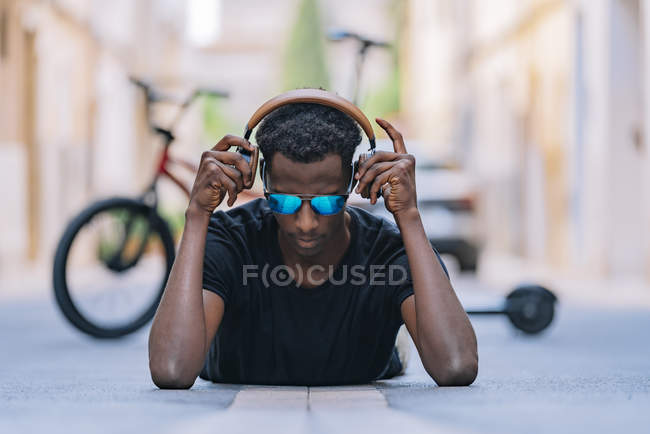 Concentrated youthful African American man in sunglasses wearing headphones and listening to music while lying on asphalt road in street — Stock Photo
