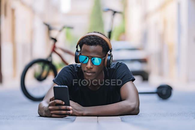 Konzentrierter junger Afroamerikaner mit Sonnenbrille, Kopfhörer und Musik auf dem Handy, während er auf der Straße liegt — Stockfoto
