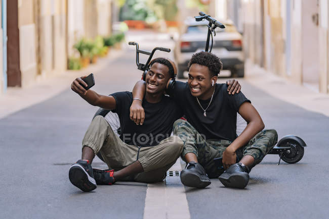 Cheerful youthful African American male teenager taking selfie pictures on cellphone with joyful black male friend in headphones — Stock Photo