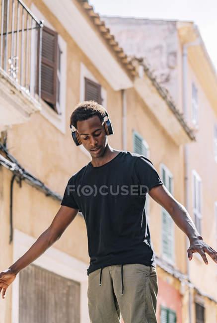 Von unten ernster junger afroamerikanischer Hipster in lässiger Kleidung und Kopfhörer, der Musik auf der Straße hört — Stockfoto