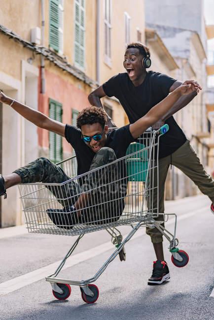 Jóvenes amigos afroamericanos sin preocupaciones y vestidos con ropa casual que andan en carro de compras por la calle. - foto de stock