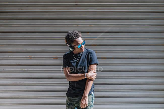 Stilvoller, moderner Afroamerikaner mit Sonnenbrille und Kopfhörer, der Musik an einer gestreiften Wand in der Straße hört — Stockfoto