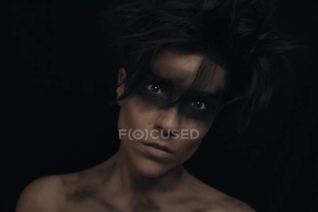 Грустная молодая темноволосая модель с нерасчесанными волосами и черным макияжем вокруг глаз, смотрящая на камеру в студии на черном фоне — стоковое фото