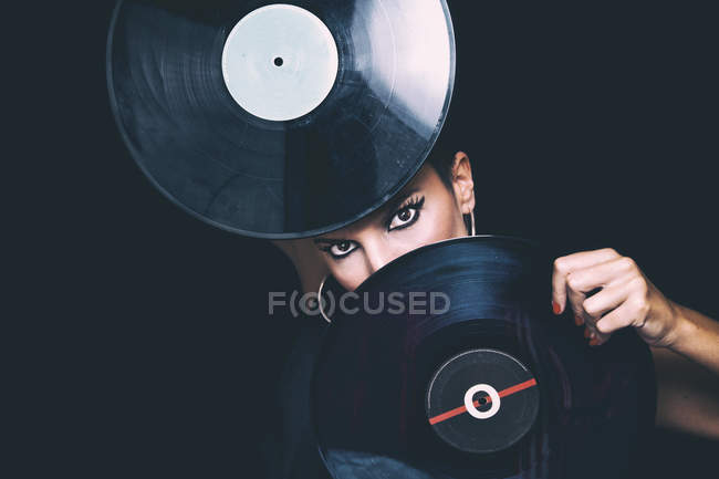 Confident young woman with bright eye liner looking at camera and hiding face behind vinyl records in studio on black background — Stock Photo