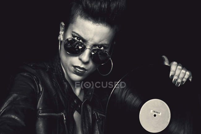 Angry confident female rocker in leather jacket and aviator sunglasses looking at camera and holding vinyl record in studio on black background — Stock Photo
