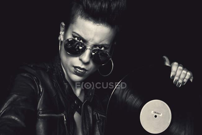 Arrabbiato rocker femminile fiducioso in giacca di pelle e occhiali da sole aviatore guardando la fotocamera e tenendo il disco in vinile in studio su sfondo nero — Foto stock