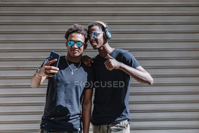 Cool jóvenes adolescentes afroamericanos en gafas de sol tomando fotos con teléfono móvil mientras se encuentran bajo la luz del sol en la calle. - foto de stock