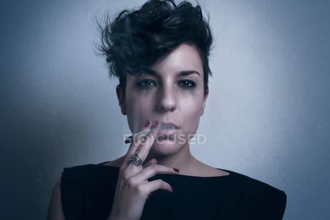 Mujer llorona pensativa infeliz con pelo corto oscuro y con ropa negra mirando a la cámara y fumando cigarrillo en el estudio sobre fondo gris - foto de stock