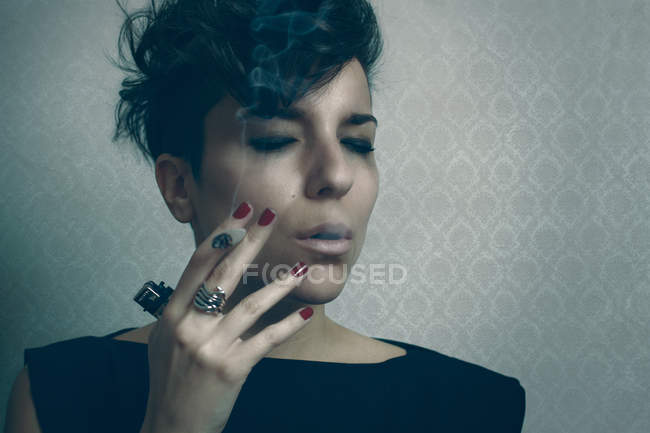 Mujer molesta fumando cigarrillo en el estudio - foto de stock