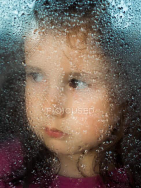 Girl behind wet window glass — Stock Photo