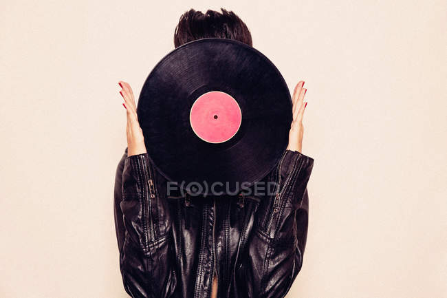 Faceless woman in leather jacket hiding face behind vinyl record in studio on pink background — Stock Photo
