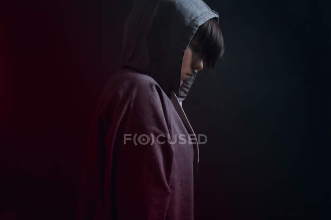 Seitenansicht einer nachdenklichen jungen Frau in grauem Känguru mit Kapuze auf schwarzem Hintergrund — Stockfoto