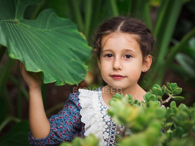 Chica escéptica comiendo fruta en el jardín - foto de stock