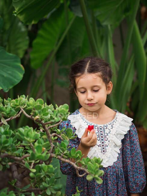Ragazza scettica mangiare frutta in giardino — Foto stock